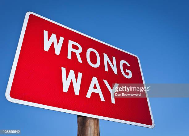 wrong way sign against blue sky - wrong way stock pictures, royalty-free photos & images