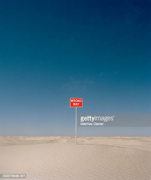 'wrong way' sign in desert - wrong way stock pictures, royalty-free photos & images