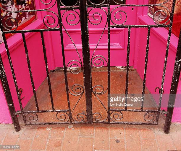 wrought iron gate and pink doorway - lyn holly coorg stock pictures, royalty-free photos & images