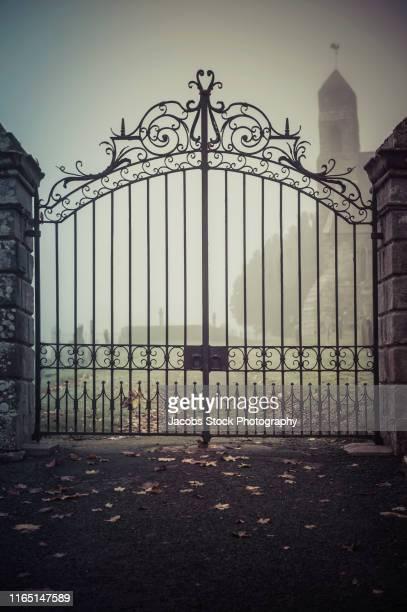 wrought iron gates into cemetery - 門 ストックフォトと画像