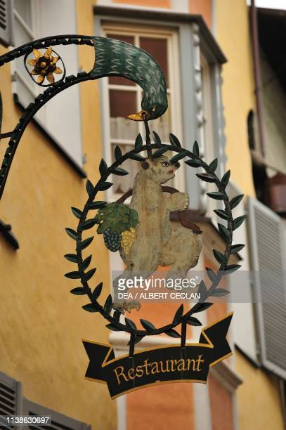 Wrought iron sign depicting a bear with grapes, of the old Grey Bear Inn, Klausen, Trentino-Alto Adige, Italy.