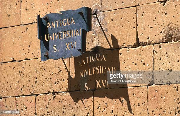 wrought-iron sign on wall of antigua universidad (old university). - universidad stock pictures, royalty-free photos & images