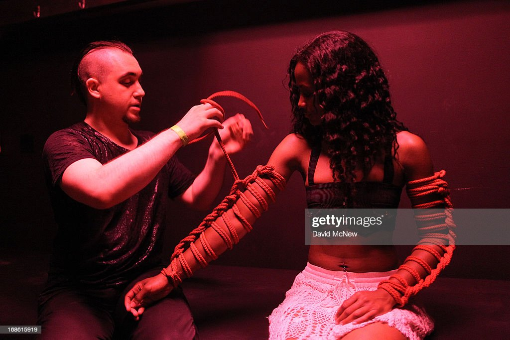 Wry practices tying knots on the arms of Wicked at a dungeon party during the domination convention, DomConLA, in the early morning hours of May 12, 2013 in Los Angeles, California. The annual convention was started in 2003 by fetish professional Mistress Cyan to bring together enthusiasts of BDSM (Bondage, Discipline, Submission and Dominance) and other fetishes.