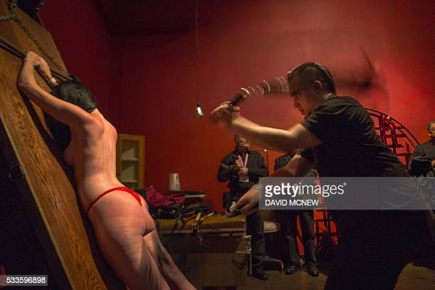 Wry whips a voluntary submissive at a dungeon party during the DomCon LA domination convention on May 21 2016 in Los Angeles California The annual...