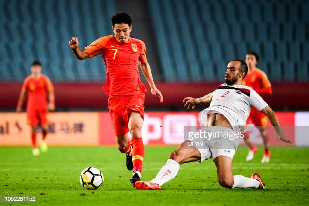 Wu Lei of China gets away from challenge from HADI ALMASRI of Syrian during the CFA Team China International Football match at Nanjing Olympic Sports...