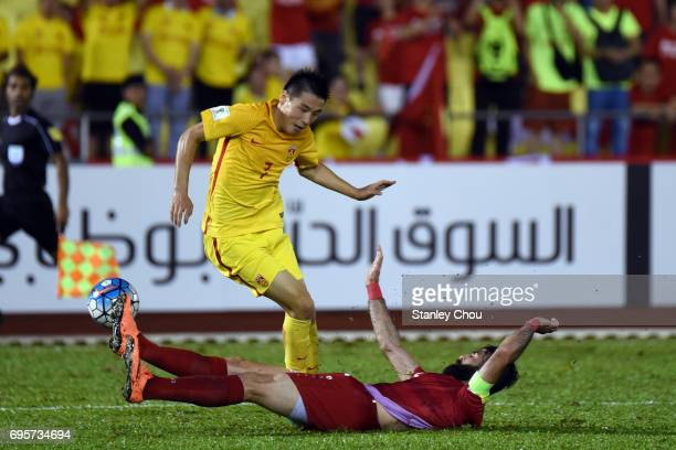 Wu Lei of China is tackled by Ahmad Al Saleh of Syria during the 2018 FIFA World Cup Asian Qualifier Group A Final Round match between Syria and...