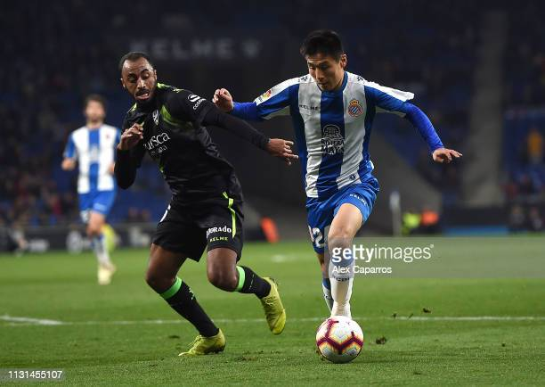 Wu Lei of Espanyol is tackled by Akapo of SD Huesca during the La Liga match between RCD Espanyol and SD Huesca at RCDE Stadium on February 22 2019...
