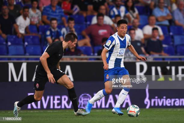 Wu Lei of Espanyol runs with the ball under pressure from Bohdan Mykhaylychenko of Zorya Luhansk during the UEFA Europa League Play Off match between...