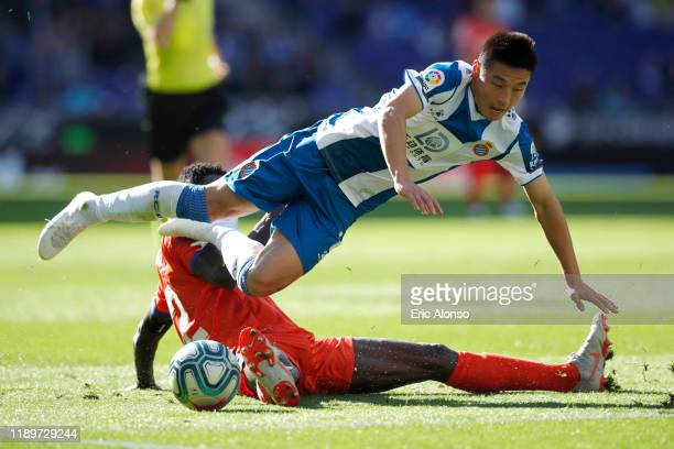 Wu Lei of RCD Espanyol is challenged by Djene Dakonam of Getafe CF during the Liga match between RCD Espanyol and Getafe CF at RCDE Stadium on...