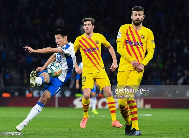 Wu Lei of RCD Espanyol shoots towards goal under a challenge by during Gerard Pique of FC Barcelona the Liga match between RCD Espanyol and FC...
