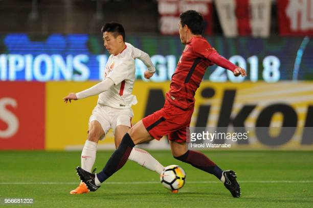 Wu Lei of Shanghai SIPG and Gen Shoji of Kashima Antlers compete for the ball during the AFC Champions League Round of 16 first leg match between...