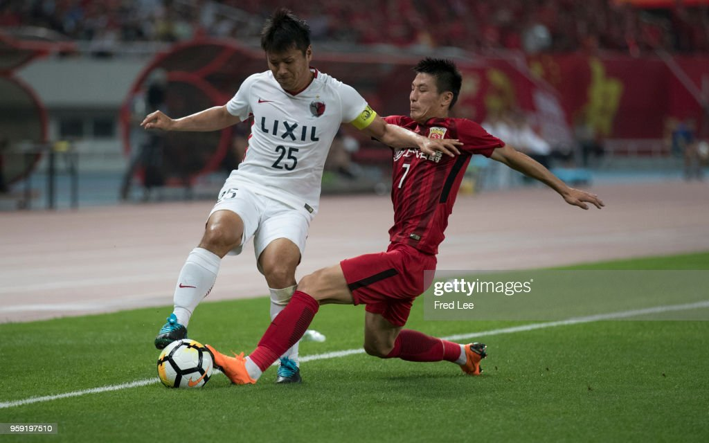 Wu Lei #7 of Shanghai SIPG and Yasushi Endo #25 of Kashima Antlers in action during the AFC Champions League Round of 16 match between Shanghai SIPG v Kashima Antlers at the Shanghai Stadium on May 16, 2018 in Shanghai, China.