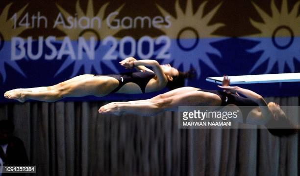 Wu Minxia and Guo Jingjing of China perform during the women's three meters sychronized diving final at Sajik pool in Busan 08 October 2002 during...