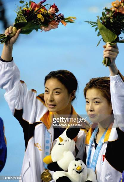 Wu Minxia and Guo Jingjing of China wave after receiving their gold medals for the women's three meters sychronized diving final at Sajik pool in...