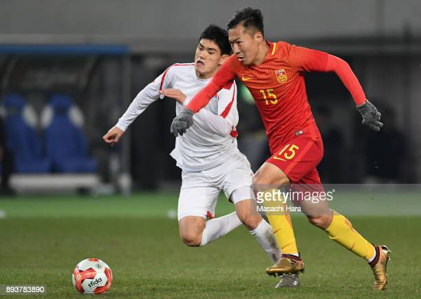 Wu Xi of China and Ri Un Chol of North Korea compete for the ball during the EAFF E1 Men's Football Championship between China and North Korea at...