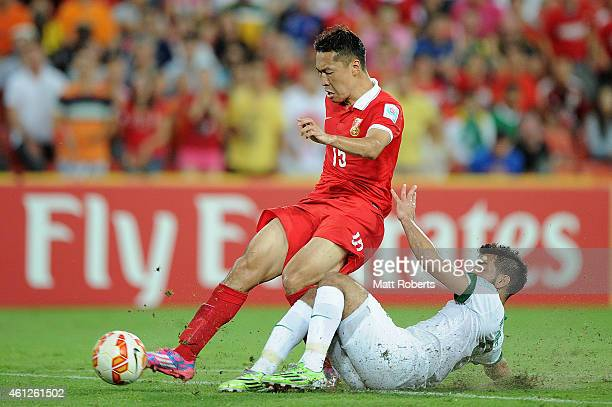 Wu Xi of China PR is tackled by Mustafa Al Bassas of Saudi Arabia during the 2015 Asian Cup match between Saudi Arabia and China PR at Suncorp...