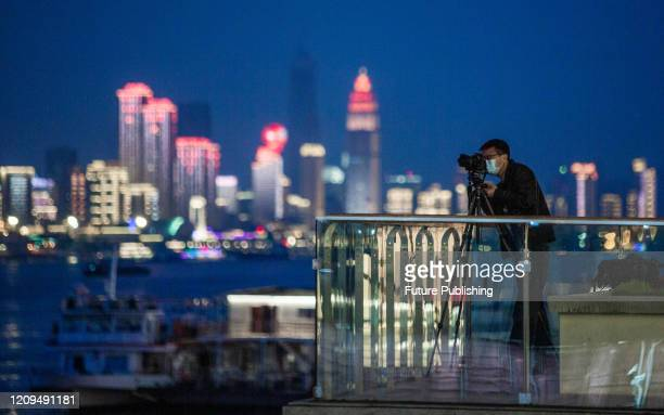 Wuhan citizen wearing a protective mask takes photos of the night scene in Wuhan Wuhan City Hubei Province April 8 2020 PHOTOGRAPH BY Costfoto /...