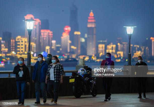 Wuhan citizens wear protective masks for a walk under the Yangtze River Bridge in Wuhan, Wuhan City, Hubei Province, April 8, 2020.- PHOTOGRAPH BY...