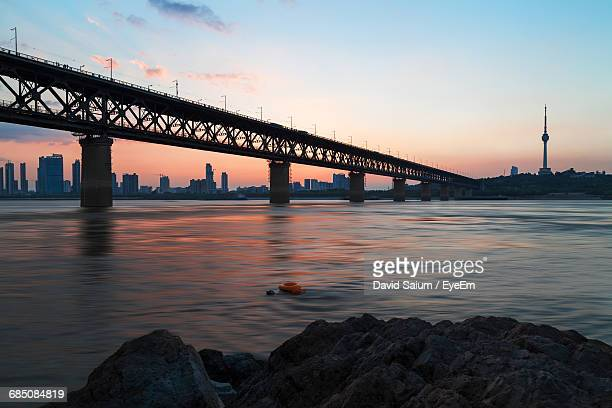 wuhan yangtze river bridge over river against tortoise mountain tv tower - wuhan stock photos and pictures
