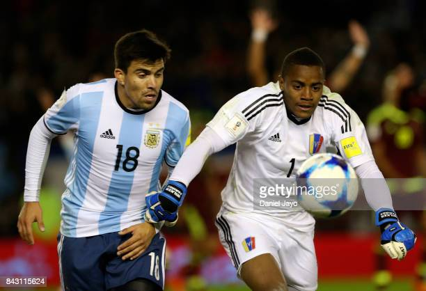Wuilker Faríñez goalkeeper of Venezuela fights for the ball with Marcos Acuña of Argentina during a match between Argentina and Venezuela as part of...