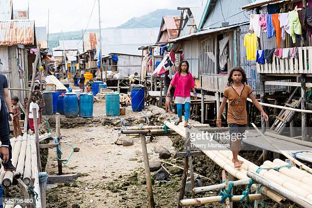 Wuring Maumere Flores Indonesia November 26 2013 Girls are walking on a bamboo bridge In 1992 the village was destroyed by a tsunami except the...