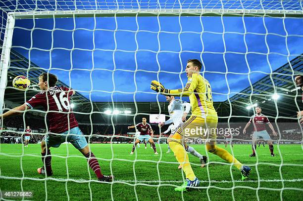 Wwest Ham player Mark Noble and goalkeeper Adrian are unable to stop a header from Bafetimbi Gomis of Swansea going into the net for the Swansea...