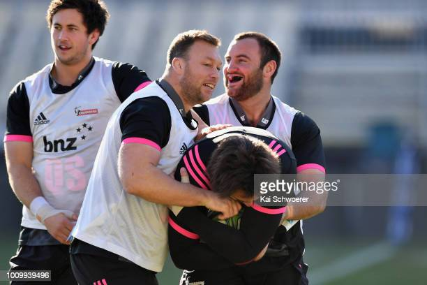 Wyatt Crockett and Tim Perry tackle Samuel Whitelock during a Crusaders Super Rugby captain's run at AMI Stadium on August 3 2018 in Christchurch New...