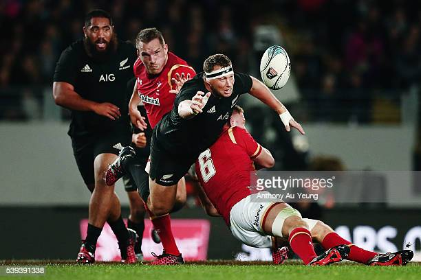 Wyatt Crockett of New Zealand offloads in the tackle from Ross Moriarty of Wales during the International Test match between the New Zealand All...