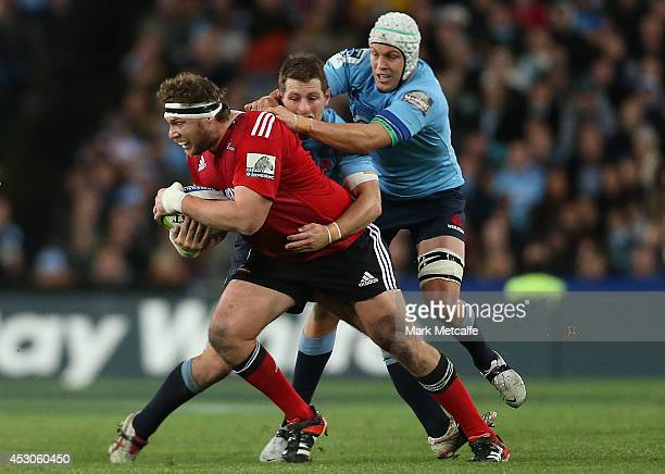 Wyatt Crockett of the Crusaders is tackled by Stephen Hoiles and Bernard Foley of the Waratahs during the Super Rugby Grand Final match between the...