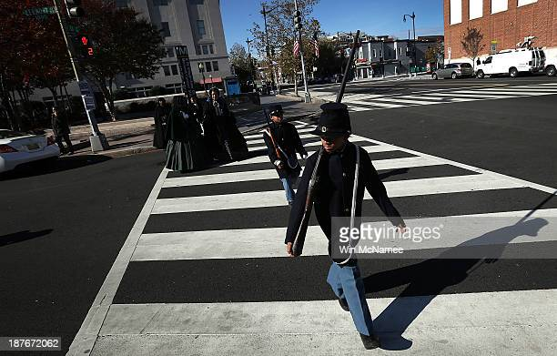 Wyatt Harris and Joshua Terry dressed in Civil War military uniforms cross the street after taking part in a wreathlaying ceremony commemorating...