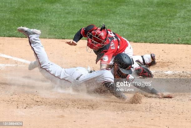 Wyatt Mathisen of the Arizona Diamondbacks slides safely into home plate ahead of the tag by Tucker Barnhart of the Cincinnati Reds in the 7th inning...