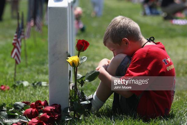 Wyatt McCain from North Pole Alaska looks upon his father's grave at the National Cemetery on Memorial Day on May 28 2012 in Arlington Virginia His...