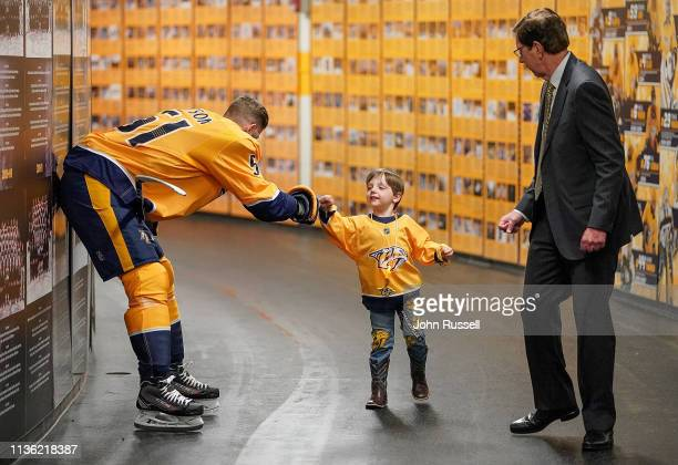 Wyatt Poile fist bumps Austin Watson of the Nashville Predators as he walks with his grandfather David Poile, general manager of the Nashville...