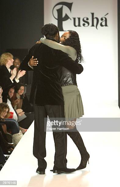 Wyclef Jean and his wife Marie Claudinette Pierre Jean appears on the runway during the Fusha Fall 2004 fashion show at Bryant Park during the...