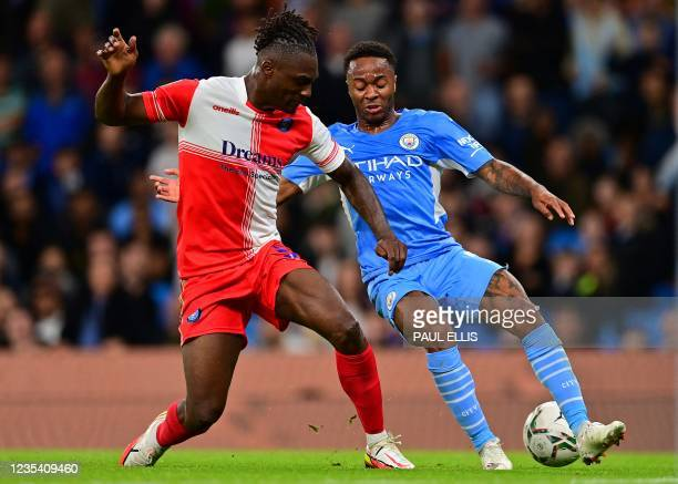 Wycombe Wanderers' English defender Anthony Stewart vies with Manchester City's English midfielder Raheem Sterling during the English League Cup...