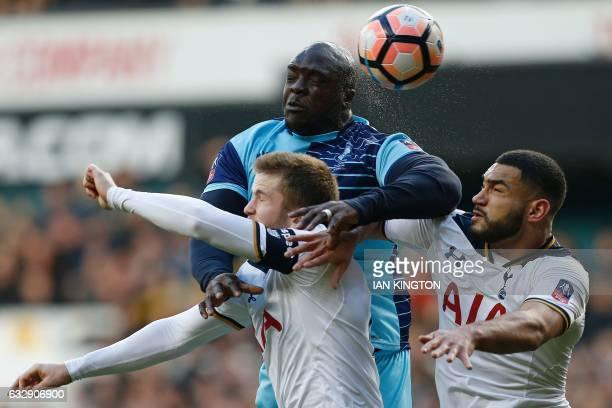 Wycombe Wanderers' English striker Adebayo Akinfenwa jumps above Tottenham Hotspur's English defender Eric Dier and Tottenham Hotspur's Englishborn...