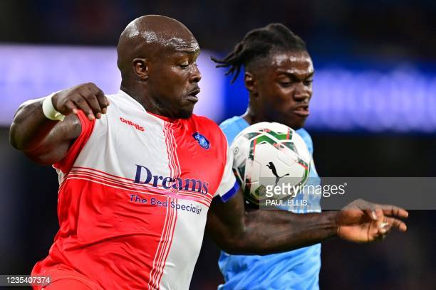 Wycombe Wanderers' English striker Adebayo Akinfenwa vies with Manchester City's Belgian defender Romeo Lavia during the English League Cup third...