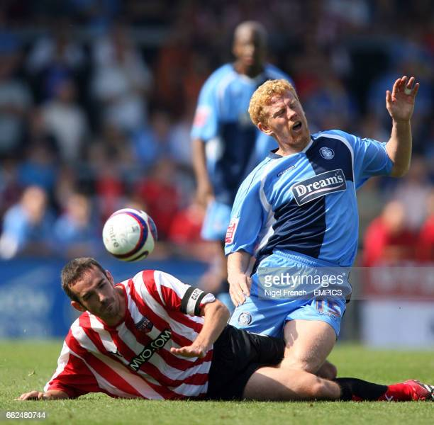 Wycombe Wanderers' Gary Holt is tackled by Brentford's Kevin O'Connor