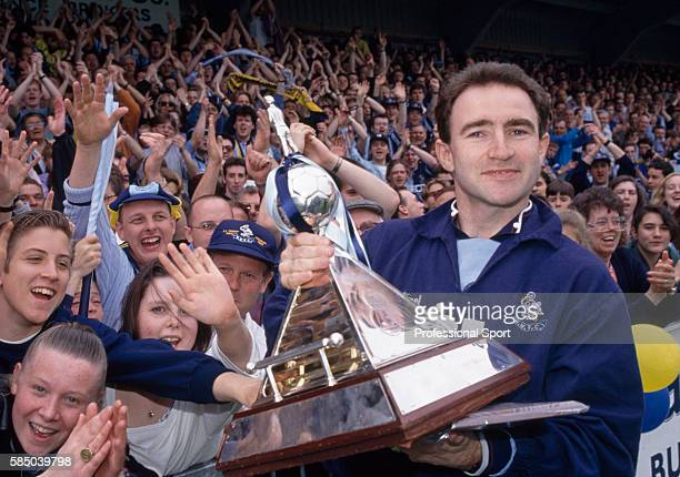 Wycombe Wanderers manager Martin O'Neill holding the Vauxhall Conference Trophy as Wycombe fans celebrate their team's promotion to the Football...