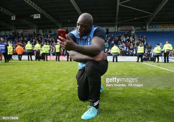 Wycombe's Adebayo Akinfenwa celebrates promotion to League One with a live video blog during the Sky Bet League Two match at the Proact...