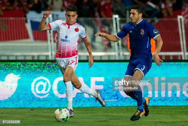 Wydad Casablanca's Achraf Bencharki vies for the ball against AlAhly's Abdallah Said during the CAF Champions League final football match between...