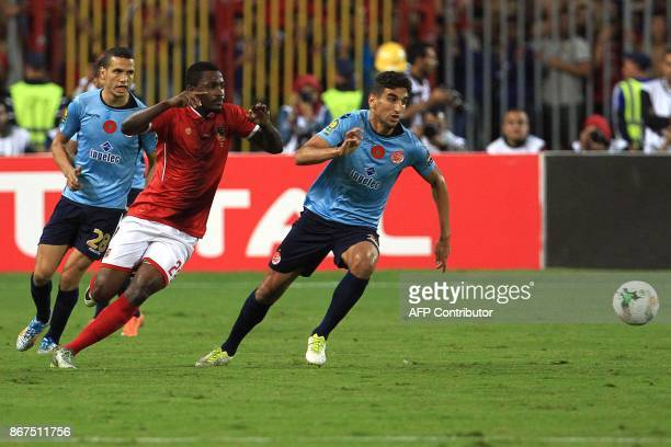 Wydad's midfielder Walid El Karti vies for the ball with Ahly's forward Junior Ajayi during the CAF Champions League final football match between...