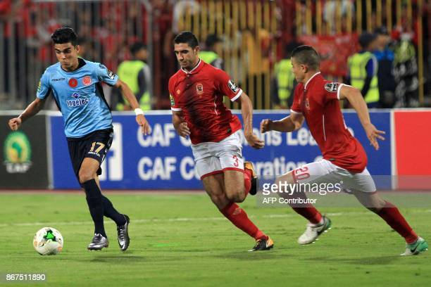 Wydad's striker Achraf Bencharki is marked by Ahly's defenders Ramy Rabia and Saad Samir during the CAF Champions League final football match between...