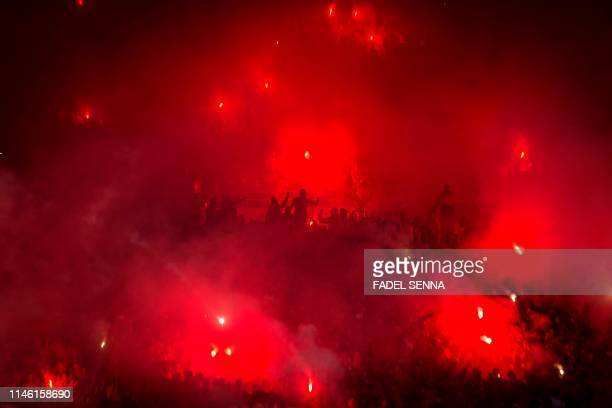 TOPSHOT Wydad's supporters light flares during the CAF champion league final 2019 1st leg football match between Morocco's Wydad Athletic Club and...