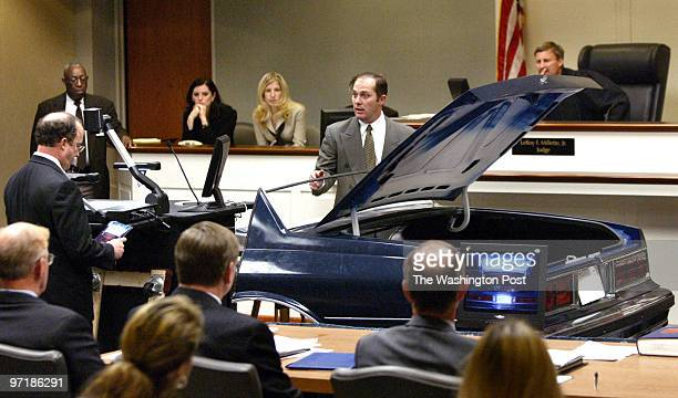 Wynn Gregory Warren , an FBI visual information specialist, gestures as he speaks near a model of the trunk area of the Chevrolet Caprice that sniper...