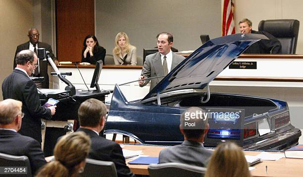 Wynn Gregory Warren an FBI visual information specialist points to a hole in a model of the trunk lid cut in the trunk of the Cheverlot Caprice that...