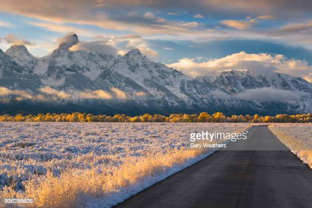 usa, wyoming, country road and teton range at sunset - ワイオミング州 ストックフォトと画像