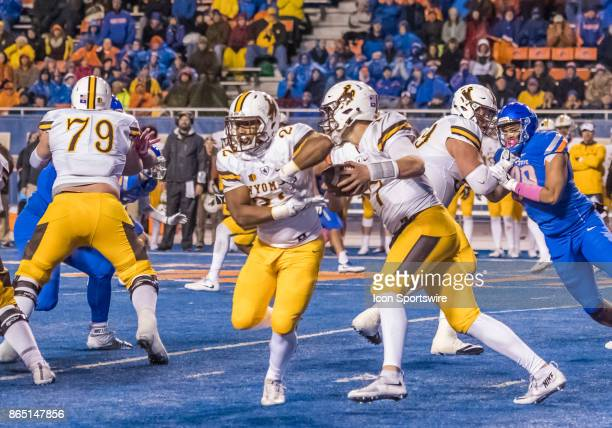 Wyoming Cowboys quarterback Josh Allen fakes a handoff to Wyoming Cowboys running back Nico Evans to take the ball up field for a Wyoming first down...