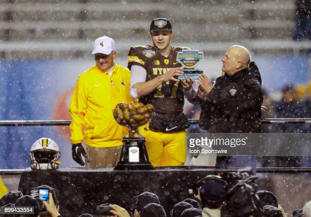 Wyoming Cowboys quarterback Josh Allen received the MVP award rom Idaho Potato Commissions CEO Frank Muir next to Wyoming Cowboys head coach Craig...