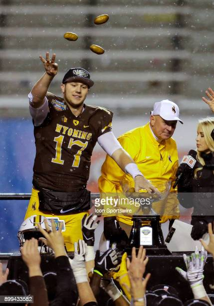 Wyoming Cowboys quarterback Josh Allen tosses Potatoes to teammates in celebration of winning the Famous Idaho Potato Bowl featuring the Central...